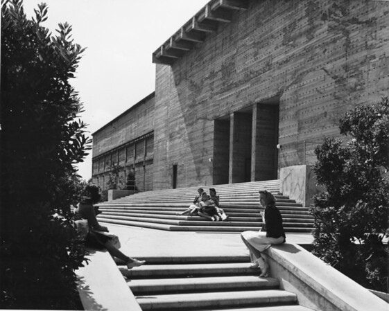 Facade of school or college with five women students sitting on front steps