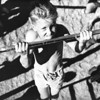 A young boy practices his chin-ups on one of many playground bars