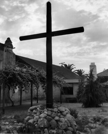 A large wooden cross standing in the garden of the San Gabriel Mission, with grape vines and one of the buildings in the background