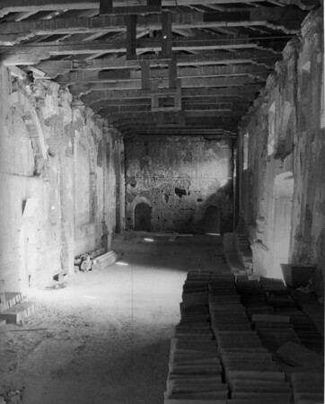 The run down interior of a San Fernando Mission building, showing adobe bricks to be used to counteract the effects of time and neglect