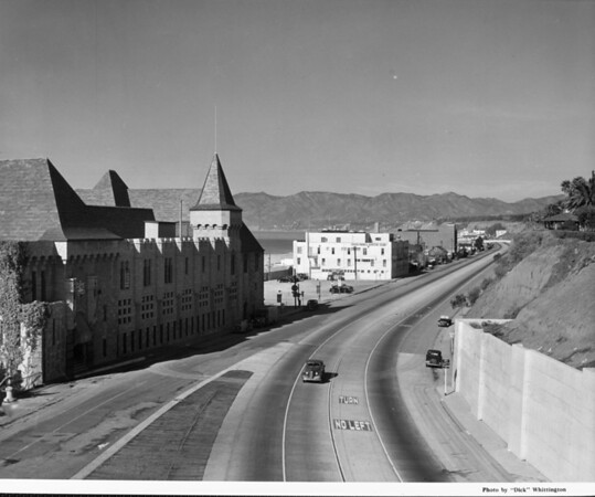 A car driving down a long stretch of road with the Santa Monica Athletic Club in the background
