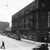Looking down the 1100 block of Main Street showing cafes, an auto wrecking company, and a tobacco company