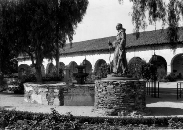 A statue of a Padre walking with an Indian child stands in front of a fountain in a courtyard at the San Fernando Mission