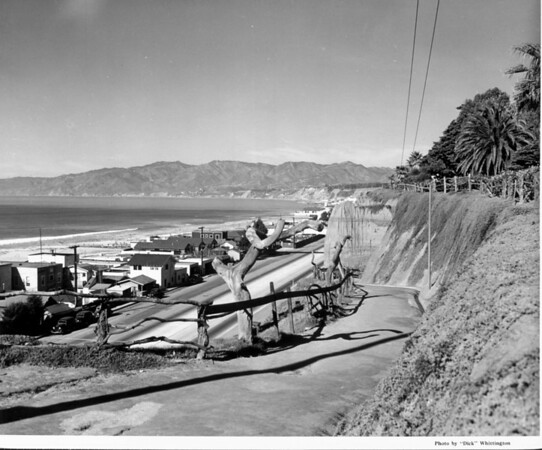 A scenic view of a row of houses along Santa Monica Beach with mountains in the background