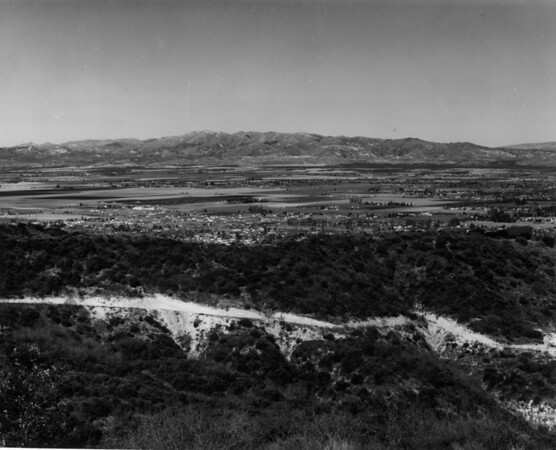 Looking over a mountain ridge with a dirt road cut into it toward the largely undeveloped San Fernando Valley