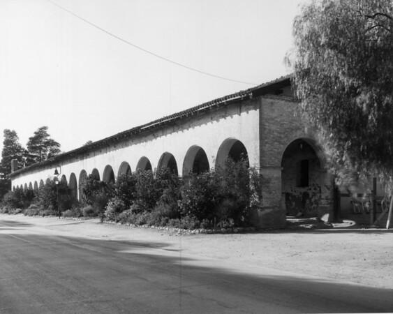 A view of the San Fernando Mission showing a mission bell guidepost used as a historical marker