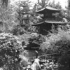 A structure surrounded by plants and trees in the Japanese gardens, with a small statue of an elephant in the foreground