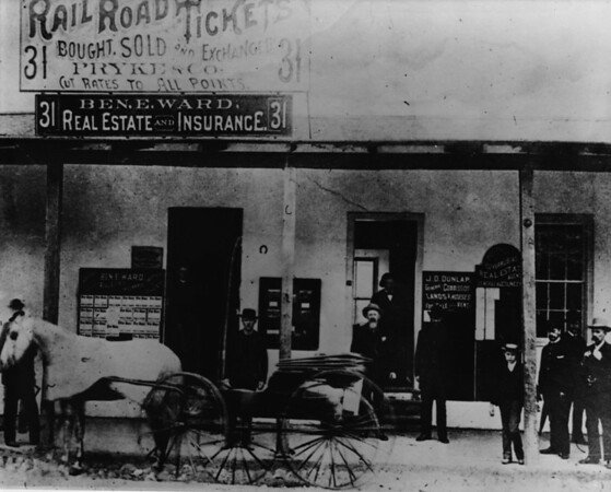 Posing in front of the store front of Ben. E. Ward Real Estate and Insurance, J.O. Dunlap Real Estate offices, and Pryke & Company Railroad Tickets