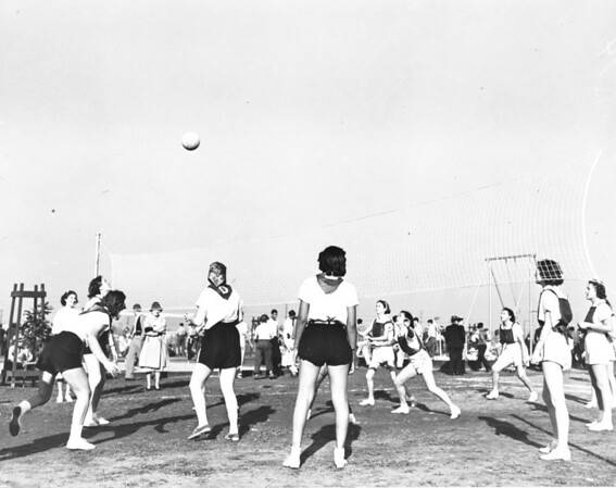 A group of women compete in a game of volleyball