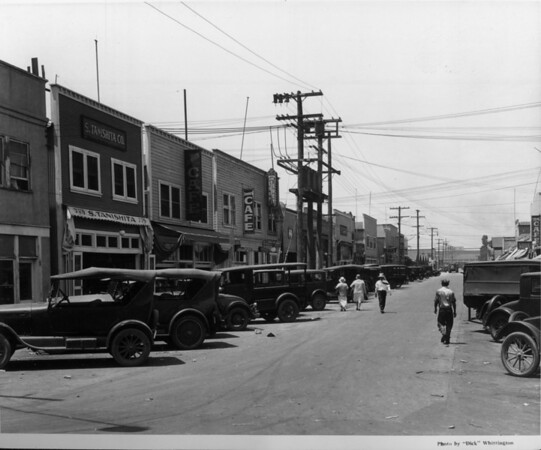 Cars parked in front of a row of cafes and chop suey restaurants in a commercial fishing area of San Pedro