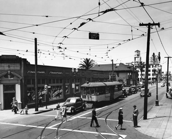 Street scene on Grand Avenue, insurance companies, auto shops pedestrians crossing street