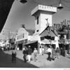 """People walking past """"Toonerville"""" in the Ocean Park Pier amusement park"""