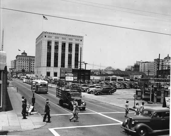 Photo of parking lot and street busy with cars and pedestrians