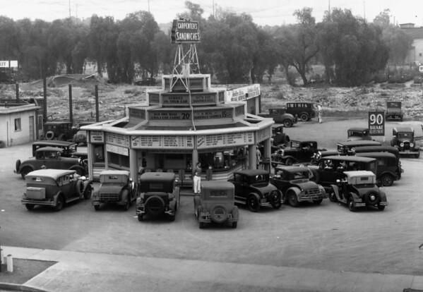 Many automobiles parked around Carpenter's Sandwiches