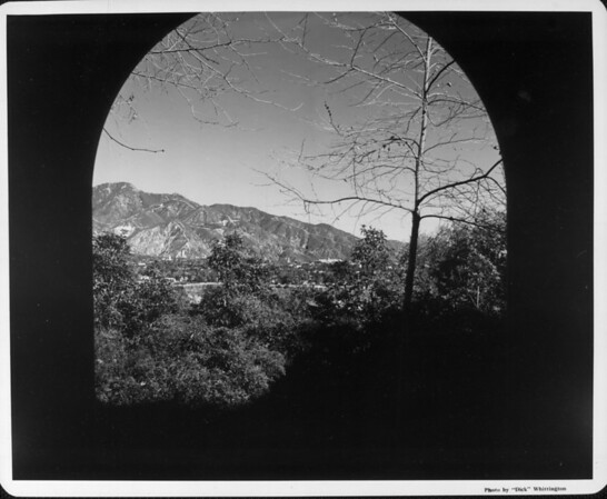 The darkness of a bridge underpass crops a beautiful landscape of trees and grass with the mountains in the background