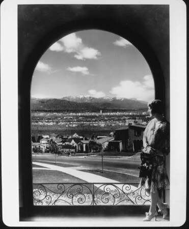 Woman looking through an arch toward downtown Los Angeles (including City Hall) in the distance