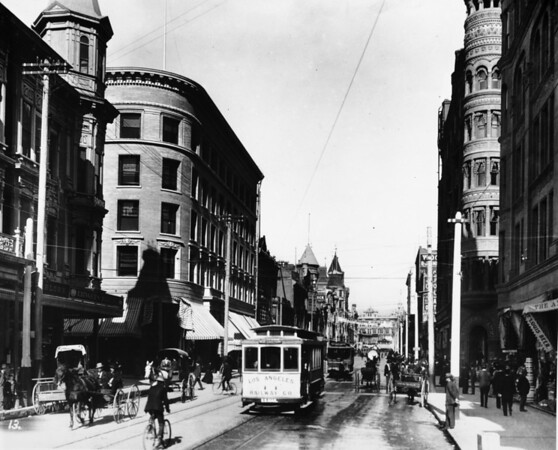 Photo of Downtown Los Angeles street with Los Angeles Railway streetcars, bicycles and horses with carriages on newly paved roads