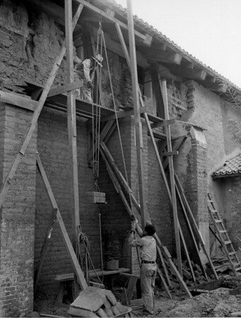 Two workers are using a rope and pulley to lift adobe bricks used in the rebuilding of a wall at the San Fernando Mission