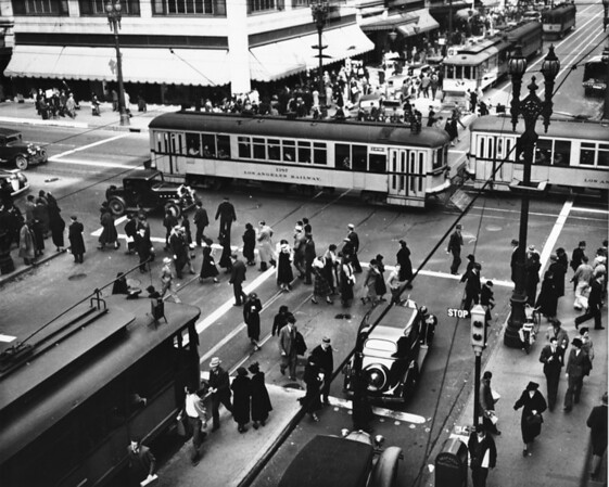 In Downtown Los Angeles at the intersection of South Broadway and West Seventh Street, crowded with pedestrians and Los Angeles Railway cars