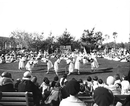 A dance troupe performs for a large crowd in the middle of Exposition Park