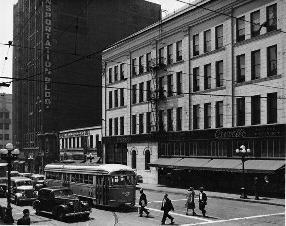 A modern looking streamlined trolley is stopped at the intersection of Seventh Street and Main Street in front of Overell's