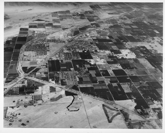 Aerial view of Indio, California, facing east on Indio Boulevard, Route 111, Whitewater River, future Indian Palms Country Club, Date Festival, County Center, Indio High School