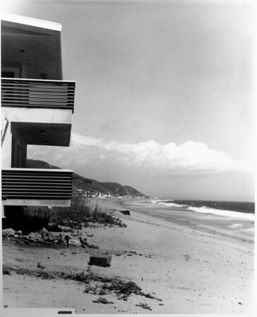 A view of a beach house right along the edge of the beach as waves rush in