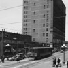 A trolley car driving down the intersection of Ninth Street and Hill Street as pedestrians walk along the sidewalk