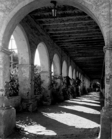 Looking down a covered walkway alongside a San Fernando Mission building, showing its brick arches and wooden roof