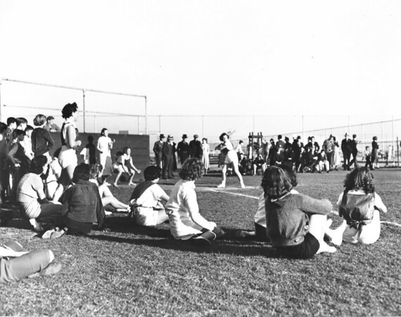 A bunch of people watch a softball game in progress, as a woman approaches the plate