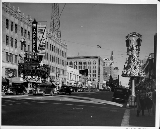 """Looking east from the corner of Hollywood Boulevard and Wilcox Avenue, with the Warner Brothers Hollywood Theatre advertising """"The Dawn Patrol"""" with Errol Flynn, and """"Nancy Drew Detective"""", ca. 1938-1939"""