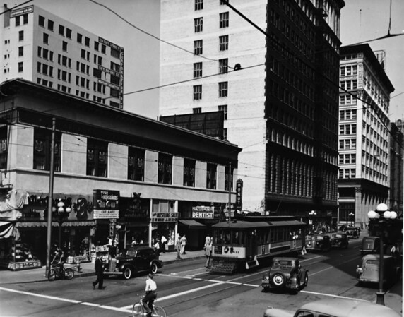 """Looking west from the intersection of Seventh Street and Main Street with many businesses including the Mill Cafe, which boasts """"The City's Best Hamburger"""""""