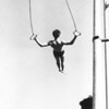 A gymnast practices his ring routine in the middle of a very busy Los Angeles playground