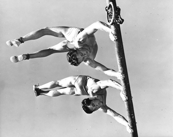 Two men practicing gymnastics from one of the playground bars