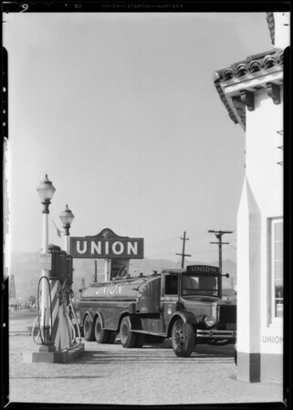 """New """"Leader"""" banner and big truck at service station for bulletin cover, Southern California, 1932"""