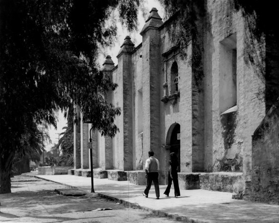A young man and woman walking past the San Gabriel Mission church, which was constructed between 1791 and 1805