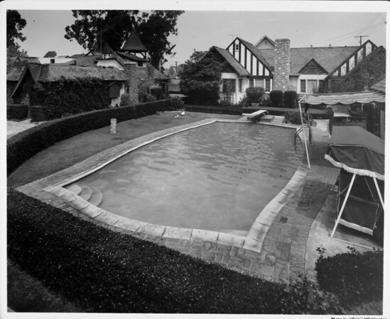 Exterior of residential home in Palm Springs in 1948, swimming pool, landscaping, patio furniture