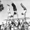 Three men practicing gymnastics on the parallel bars, as many young onlookers cheer them on