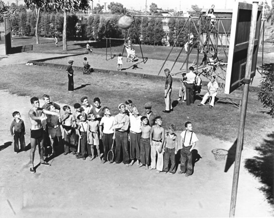 A group of young men line up to shoot some basketballs, while other kids play on the swing set in the background