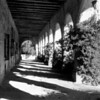 A view of a covered walkway alongside a San Fernando Mission building, showing a doorway and iron bars on the windows