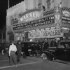 "Automobiles parked in front of the theater and people entering the Warner Brothers Theatres for the premiere of ""The Private Lives of Elizabeth of Essex"""