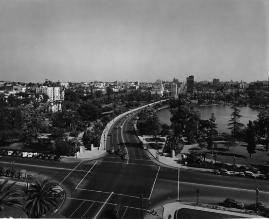 Aerial view of MacArthur Lake in MacArthur Park facing east along Wilshire Boulevard from South Park View Street towards Alvarado Street and the Westlake Theater