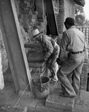 Two workers restoring part of the San Fernando Mission by rebuilding a wall with adobe bricks