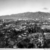 A panoramic [aerial] view of the Glendale skyline, showing a residential neighborhood in the foreground and a clear view of the mountains in the back