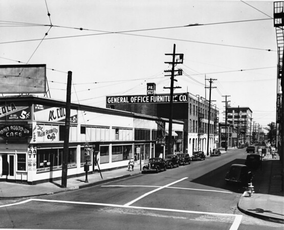 Corner of Main Street and West Eleventh Street showing restaurant and furniture store on Eleventh Street and a large advertisement for RC Cola on the outside wall of a restaurant