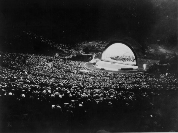 A view of a nightime concert from the audience, with the parking lot visible behind the stage