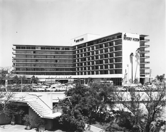 Facade of the Beverly Hilton foregrounded by its parking lot