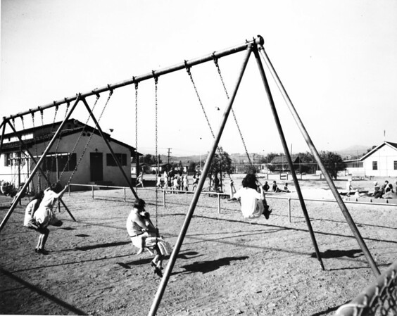 Mothers and their children play on the swing set, as other children play in the sandlot
