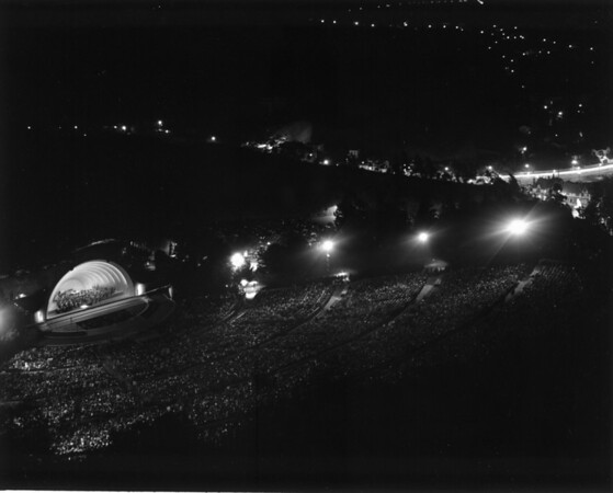 A view of a nightime concert at the Hollywood Bowl, with houses and a brightly lit street visible in the background