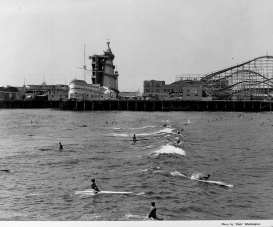 People ride surf boards and paddle boards in front of an amusement park